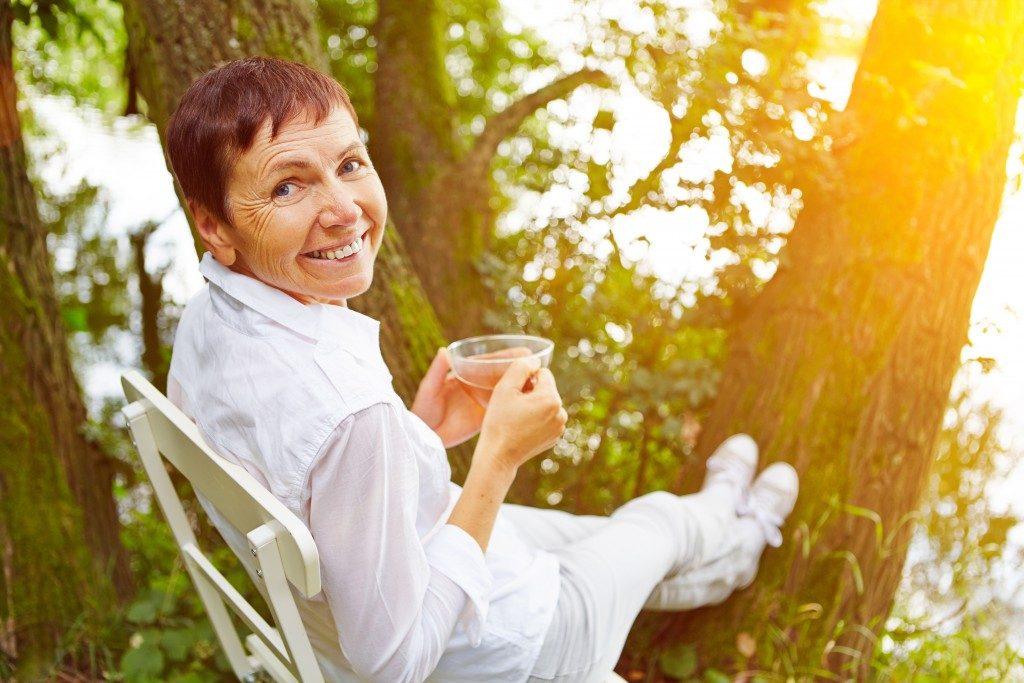 Elderly woman having her tea outdoors