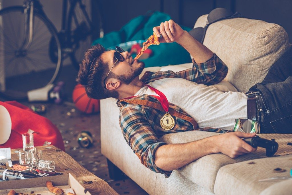 Man eating pizza while playing video games