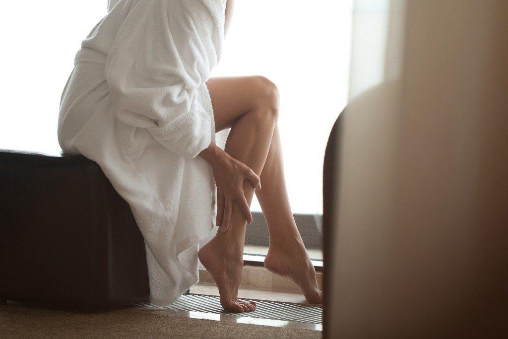 Woman massaging her leg