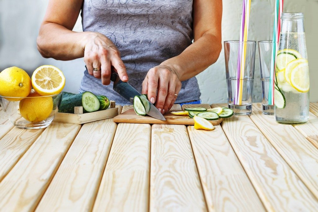 woman chopping up cucumbers and lemons