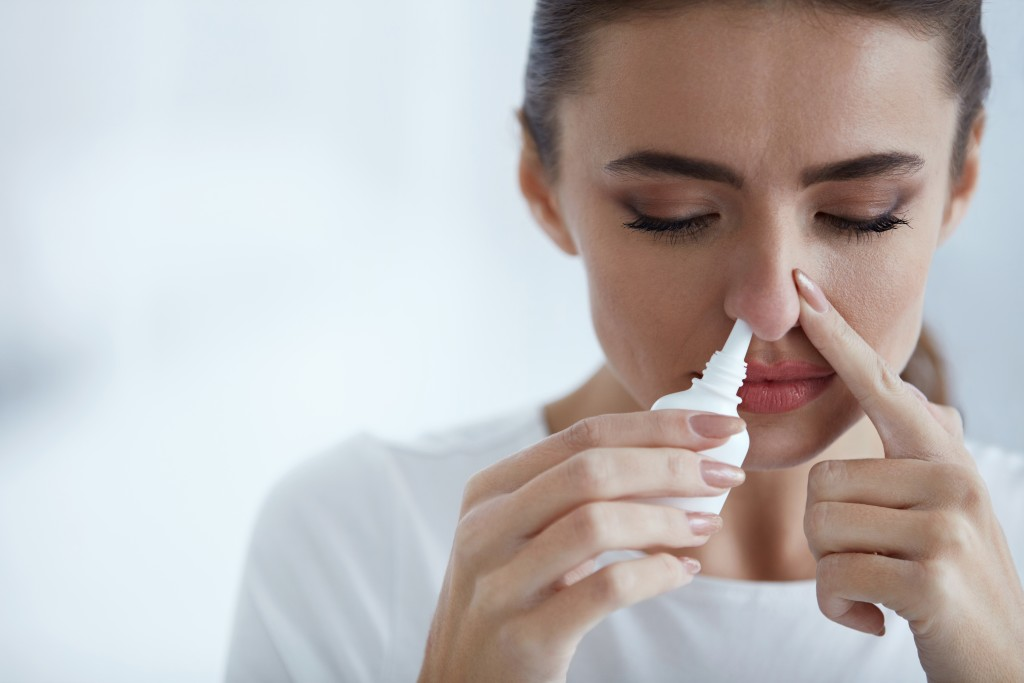 Woman sniffing a nasal spray