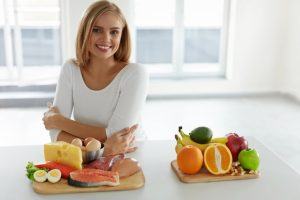 woman with fresh fruits and ingredients for her diet
