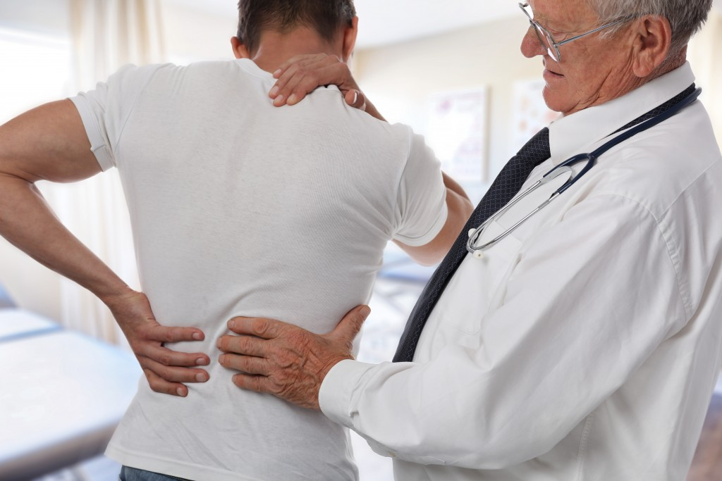 Doctor examining a patient with back pain