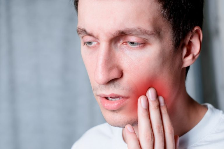Man touching left cheek with a canker sore