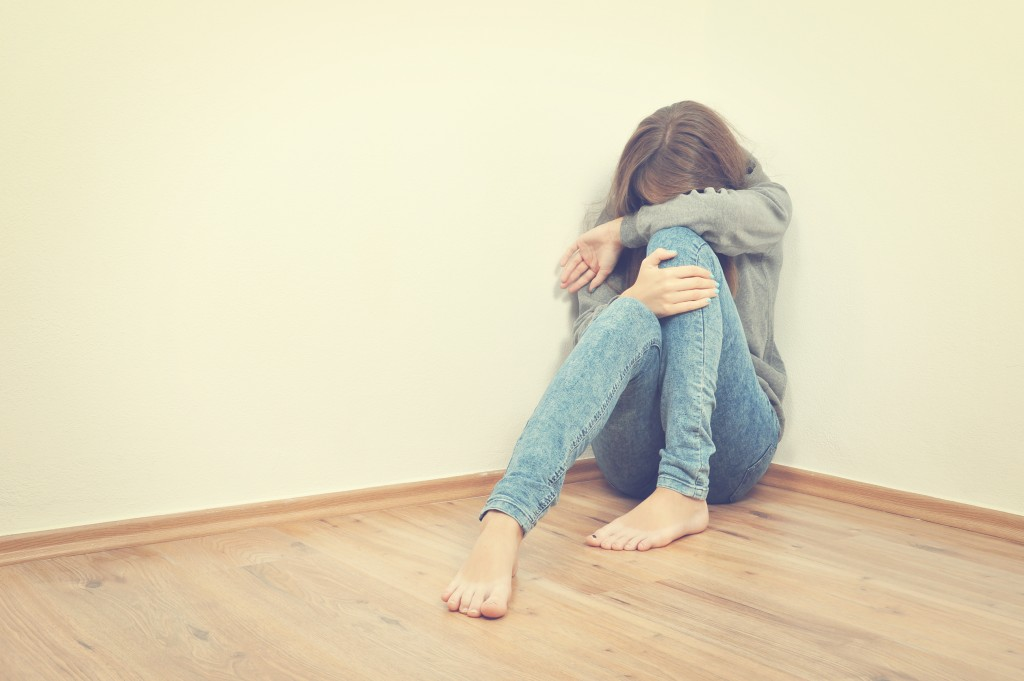 Depressed teenager sitting in the corner