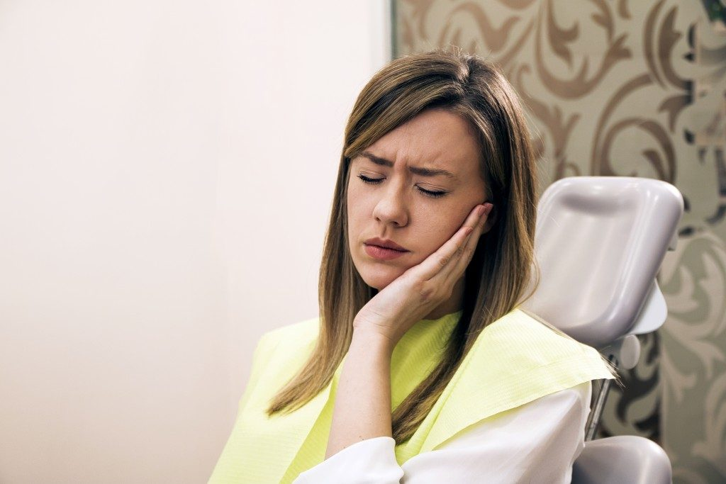 woman having a hard time with her damaged teeth