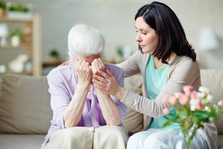 daughter consoling her upset elder mom