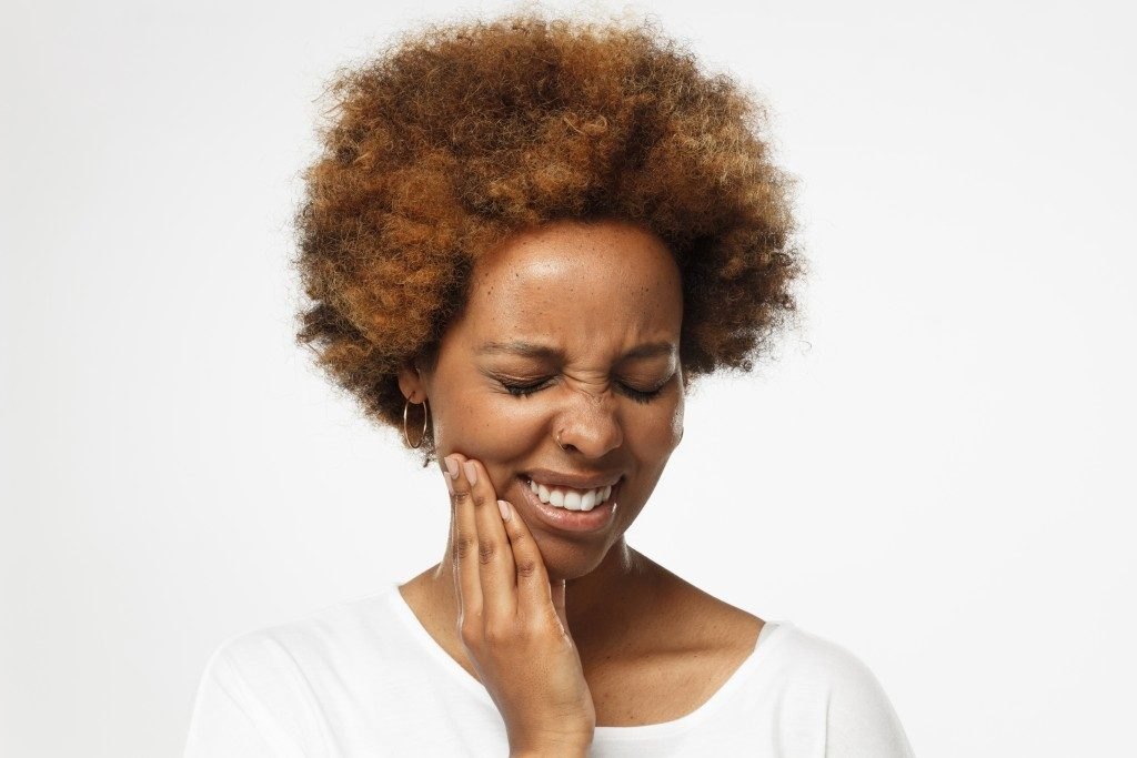 woman reacting to tooth sensitivity