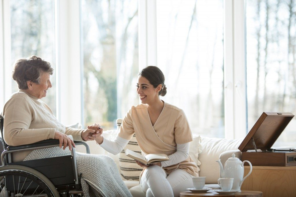 Doctor in hospice talking to elderly woman