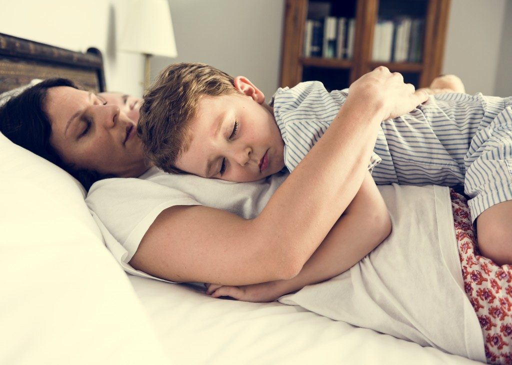 Mother hugging her son while sleeping