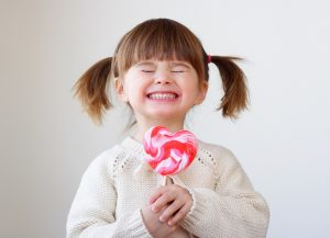 little kid smiling with a pink candy in hand