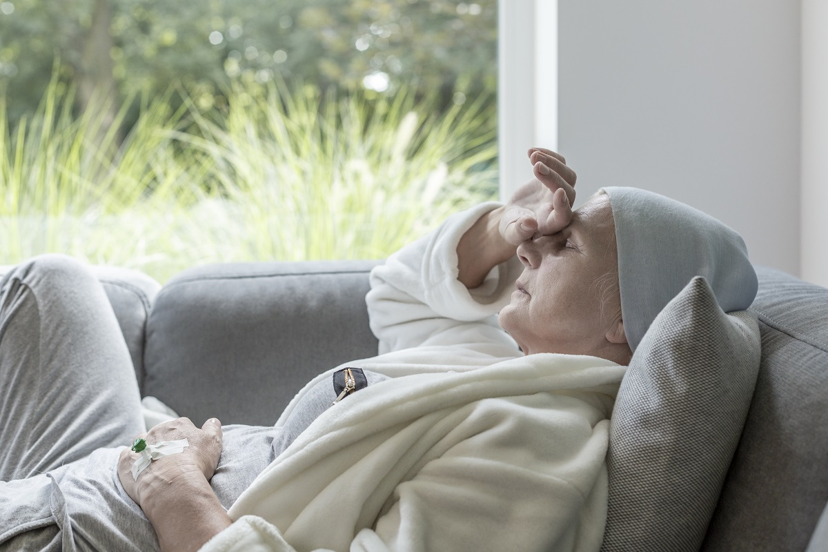 Sick senior with a hand on a forehead lying on a sofa
