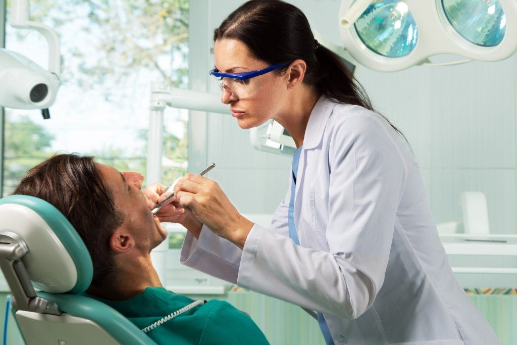 dentist checking her patient's teeth
