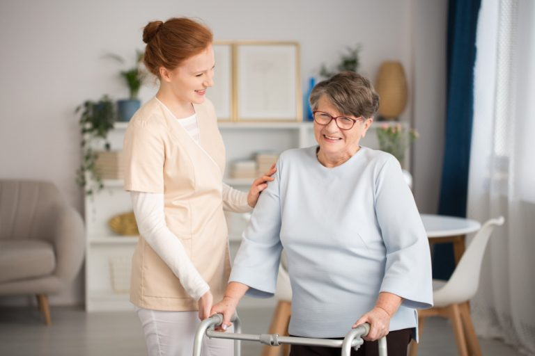 Caretaker assisting elderly to walk