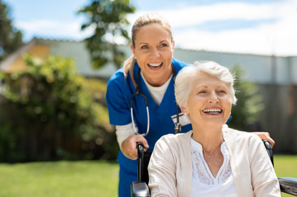 Female caregiver and senior citizen on wheelchair