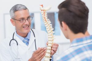 doctor showing spine model to patient